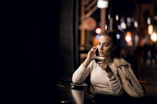 Ragazza con il telefono durante la notte