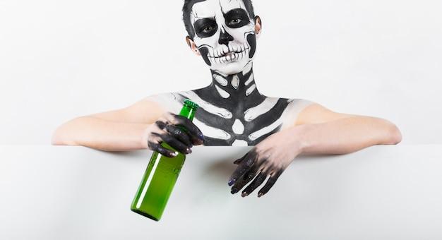 Ragazza con il trucco scheletro tenere la bottiglia di vetro verde