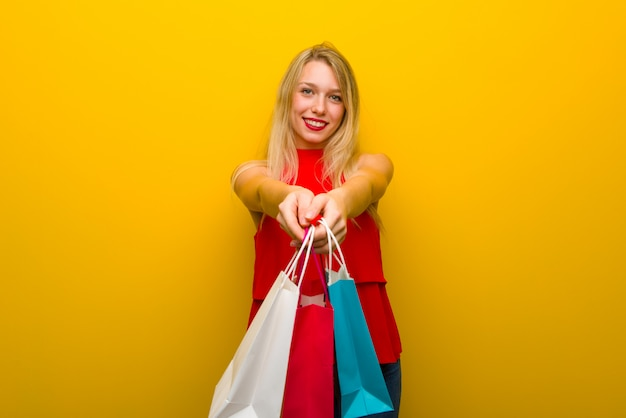 Ragazza con il vestito rosso sopra la parete gialla che tiene molti sacchetti della spesa