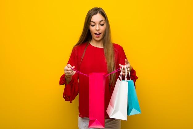 Ragazza con il vestito rosso sopra la parete gialla sorpresa mentre tenendo molti sacchetti della spesa