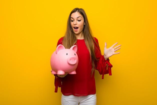 Ragazza con il vestito rosso sopra la parete gialla sorpresa mentre tenendo un porcellino salvadanaio