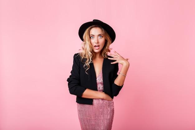Ragazza con il viso a sorpresa in piedi sul muro rosa. indossa un abito elegante con paillettes. emozioni stupite indossa un vestito alla moda con sequenza, giacca e cappello neri.