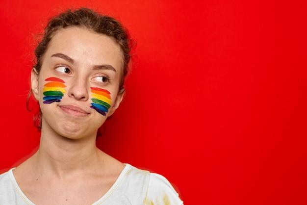 Ragazza con la bandiera dell'orgoglio dipinta sul suo sorridere delle guance