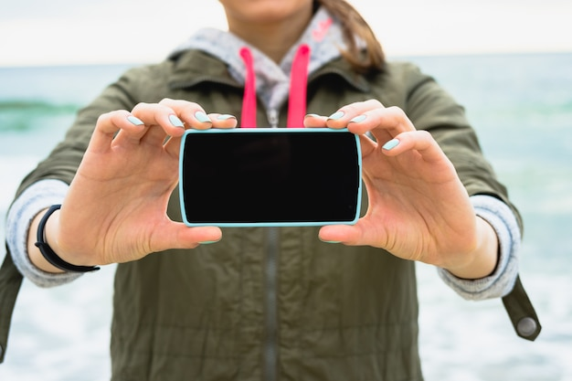 Ragazza con la giacca verde mostra uno schermo del telefono vuoto su uno sfondo del mare