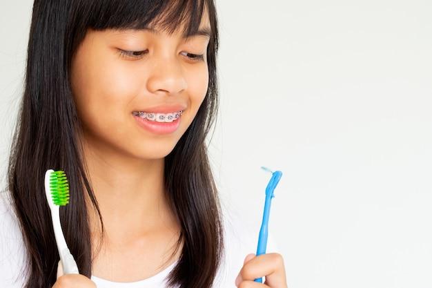 Ragazza con la mano dei denti delle parentesi graffe che tiene spazzolino da denti che sorride e felice