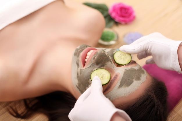 Ragazza con la maschera facciale che si trova nel centro della stazione termale di salute di bellezza