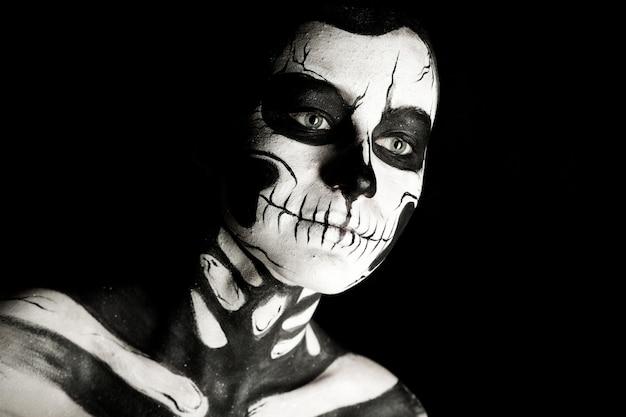 Ragazza con la pittura del corpo scheletro trucco