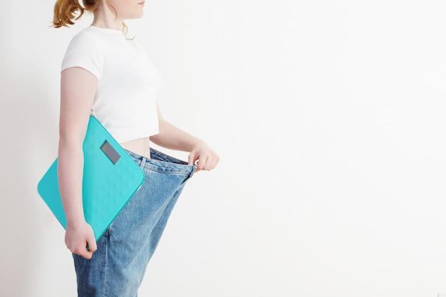 Ragazza con la scala che tira i suoi grandi jeans e che mostra perdita di peso