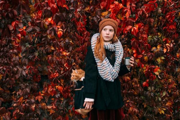 Ragazza con la tazza di tè nel suo gatto di trasporto della mano dentro la sua borsa nel parco di autunno