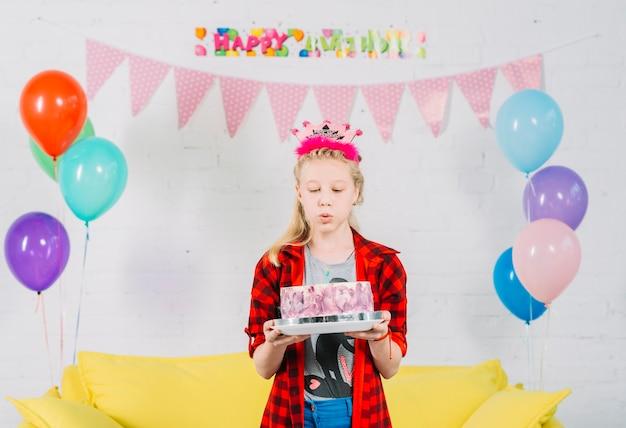 Ragazza con la torta di compleanno soffiando la candela