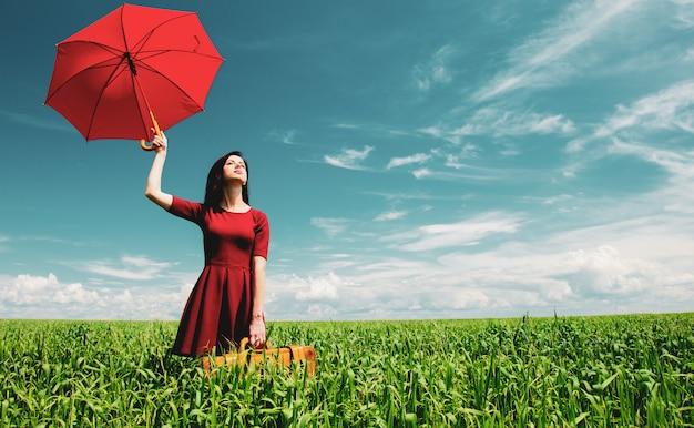 Ragazza con la valigia e ombrello al campo di grano