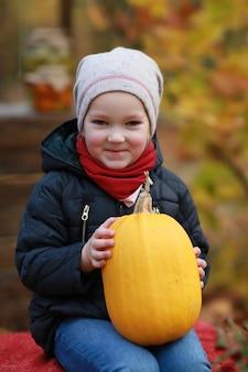 Ragazza con la zucca in autunno parco