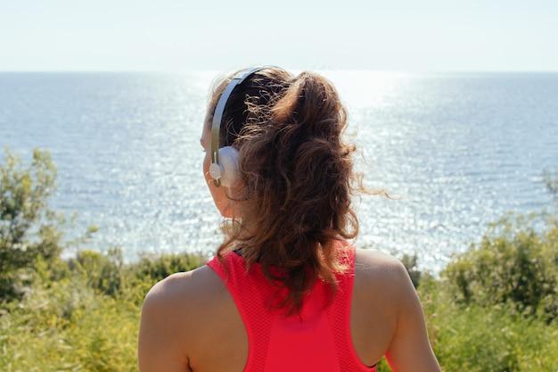 Ragazza con le cuffie e una canottiera rossa guardando il mare in estate, la vista dalla parte posteriore