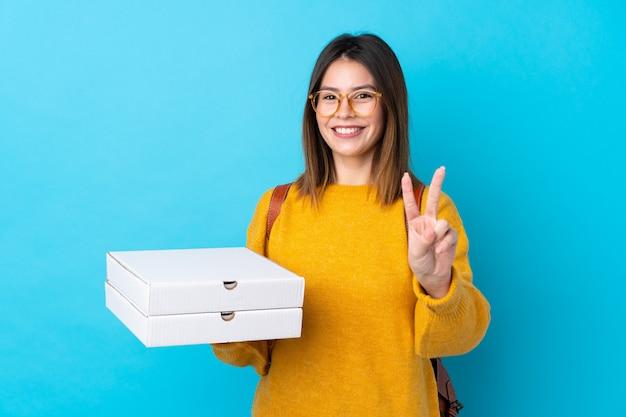 Ragazza con le pizze sopra la parete blu