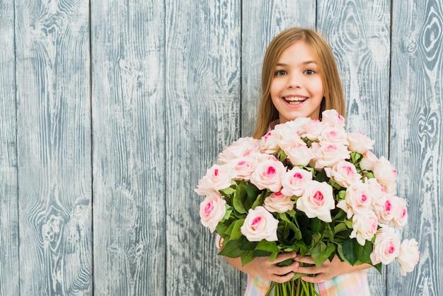 Ragazza con le rose della holding del viso sorpreso felice
