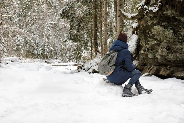 Ragazza con lo zaino che si siede in una foresta di conifere innevata.