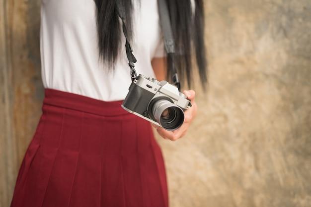 Ragazza con macchina fotografica d'epoca nelle mani