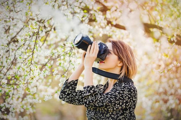 Ragazza con macchina fotografica professionale, rendendo le immagini di un albero in fiore