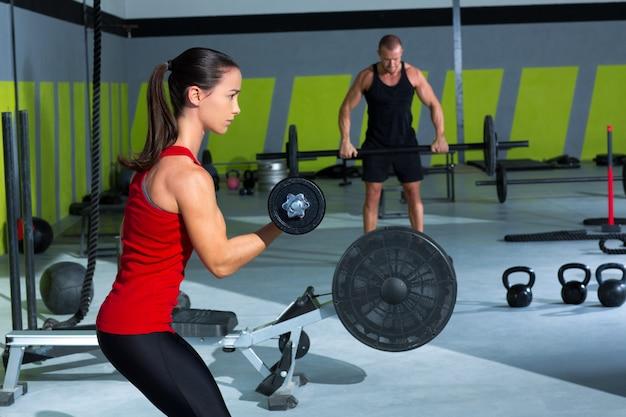 Ragazza con manubri e man weightlift bar allenamento