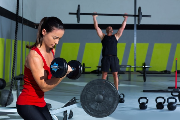 Ragazza con manubri e man weightlift bar allenamento