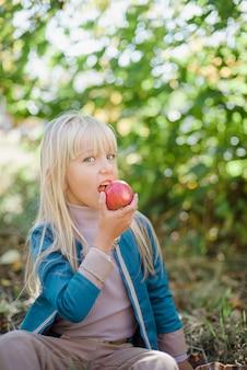 Ragazza con mela nel frutteto. harvest concept.