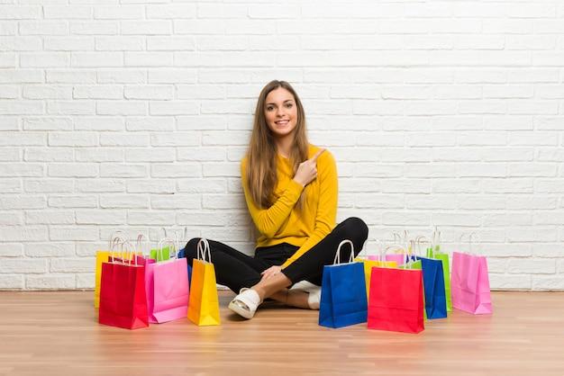 Ragazza con molti sacchetti della spesa che indica il lato per presentare un prodotto