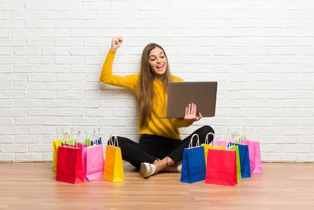 Ragazza con molti sacchetti della spesa con il computer portatile e celebrare una vittoria