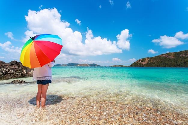Ragazza con ombrello pieno di colore sulla spiaggia sabbiosa