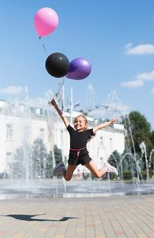 Ragazza con palloncini alla fontana