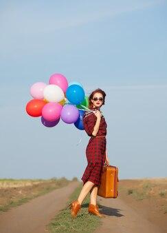 Ragazza con palloncini multicolori e borsa