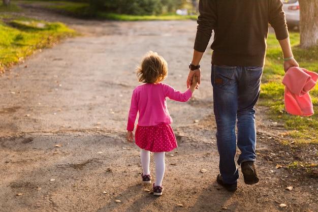 Ragazza con papà per una passeggiata, il sole al tramonto. famiglia e tempo con la famiglia, relazioni familiari, cura