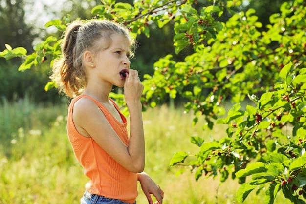 Ragazza con piacere che mangia le bacche mature dolci deliziose dall'albero di gelso