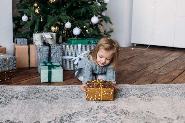 Ragazza con regalo di natale, albero di natale