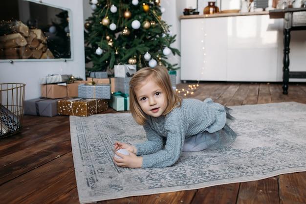 Ragazza con scatole regalo e albero di natale sullo sfondo
