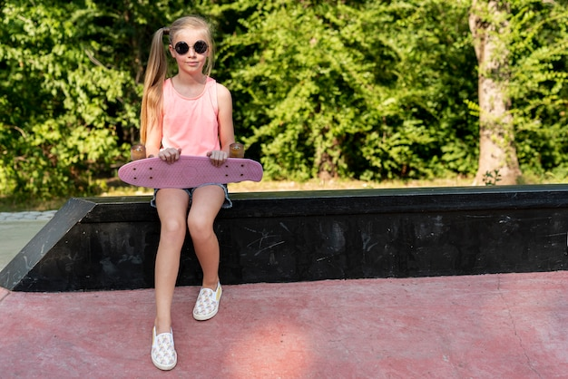 Ragazza con skateboard rosa e occhiali da sole