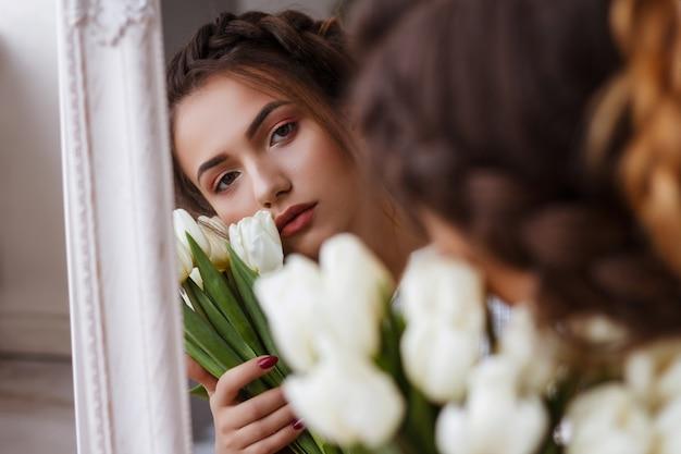 Ragazza con tulipani bianchi in studio riflesso nel ritratto specchio. look estivo. trucco e acconciatura. bruna. foto tenera