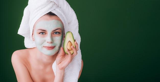 Ragazza con un asciugamano bianco in testa con una nutriente maschera verde sul viso e un avocado in mano su uno sfondo verde con spazio per il testo