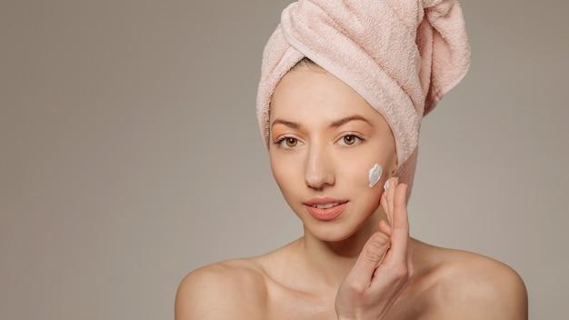 Ragazza con un asciugamano sulla testa usando la crema