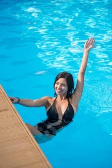 Ragazza con un bel sorriso in una piscina