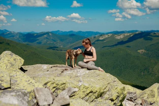 Ragazza con un cane in cima a una montagna a guardare un bellissimo paesaggio con le braccia spalancate