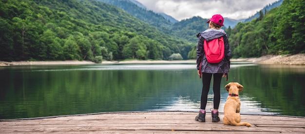 Ragazza con un cane in piedi sul molo sul lago