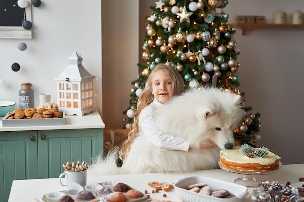Ragazza con un cane vicino all'albero di natale a natale