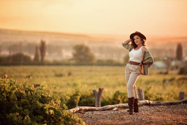 Ragazza con un cappello da cowboy al tramonto in campagna tra i vigneti.