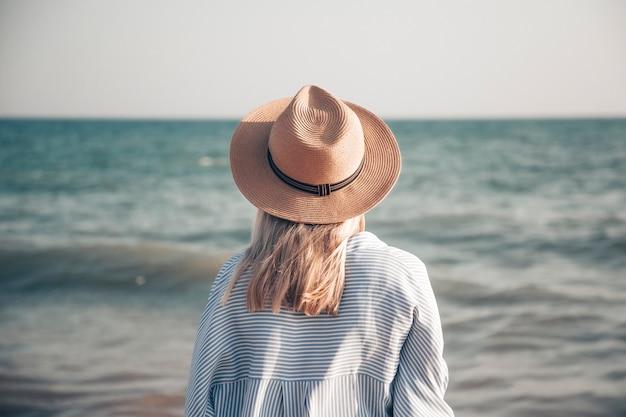 Ragazza con un cappello di paglia e una camicia sulla spiaggia. vista posteriore