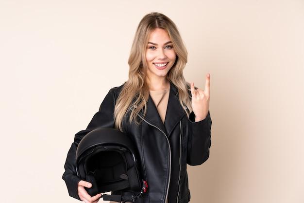 Ragazza con un casco da motociclista sulla parete beige che fa gesto di roccia