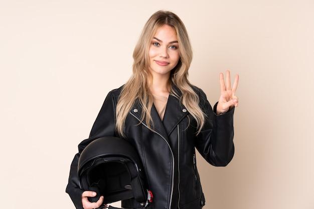 Ragazza con un casco da motociclista sulla parete beige felice e contando tre con le dita
