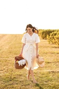 Ragazza con un cesto di vimini in mano tra i campi.