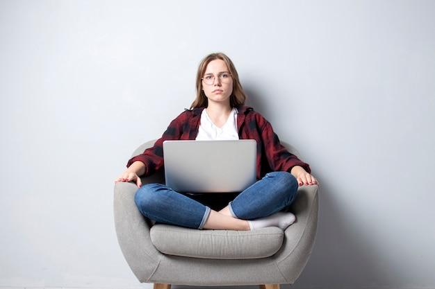 Ragazza con un computer portatile seduto su una sedia morbida e confortevole