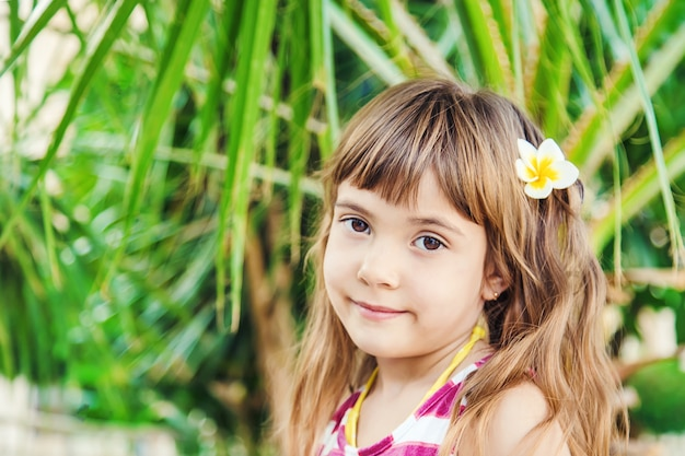 Ragazza con un fiore di plumeria tra i capelli sullo sfondo delle palme. messa a fuoco selettiva