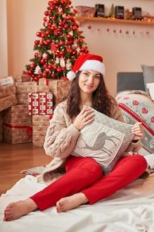 Ragazza con un regalo a casa nell'interno del nuovo anno